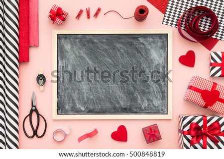 Blackboard and presents wrapped on a mint color background with different on a pink color table. Flat lay.Christmas (xmas) or New year gift packing. Holiday decor concept.