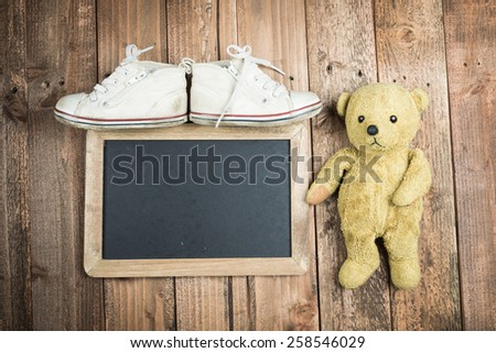 Blackboard and teddy bear and children's shoes - stock photo