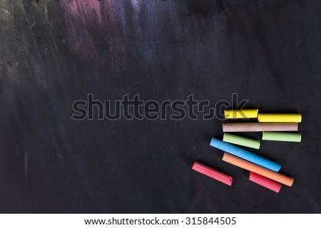 Blackboard and various colors of chalk - stock photo