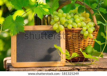 Blackboard blank and bunch of grapes against green spring background - stock photo