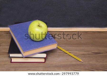 blackboard, books and apple on desk - stock photo