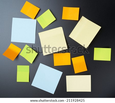 Blackboard covered with multiple copyspace empty sticky paper notes - stock photo
