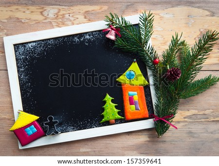 Blackboard decorated with colorful christmas  cookies and fir tree branch  - stock photo