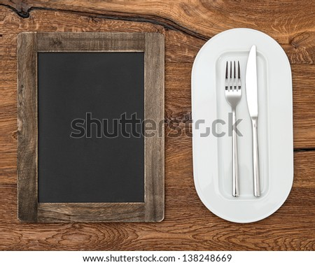 blackboard for menu on wooden table with white plate, knife and fork