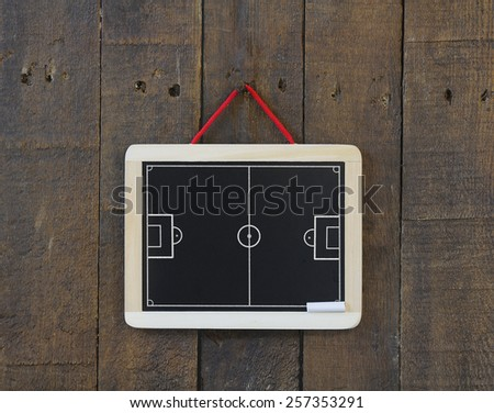 Blackboard hanging on a wall with football field. - stock photo
