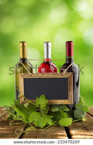 blackboard hanging on wine bottles and grapevine leaves - stock photo
