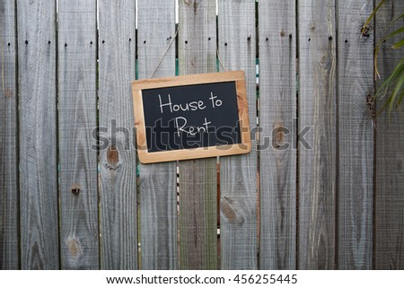 Blackboard house to rent sign on wooden fence - stock photo