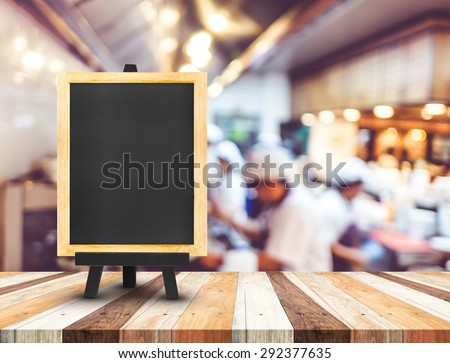 Blackboard menu with easel on wooden table with blur open kitchen at  restaurant background, Copy space for adding your content - stock photo