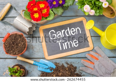 Blackboard on a plant table with garden tools - Garden Time - stock photo