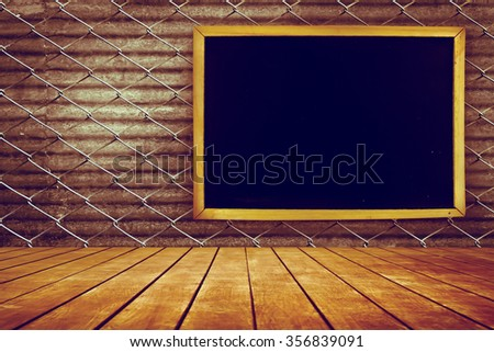 blackboard on net fence and old perspective wooden floor with black rusty galvanized iron background