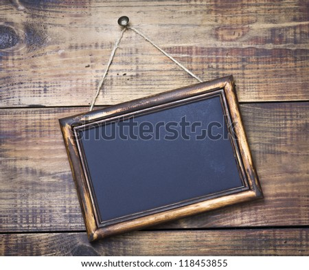 Blackboard on wooden background with space for text - stock photo