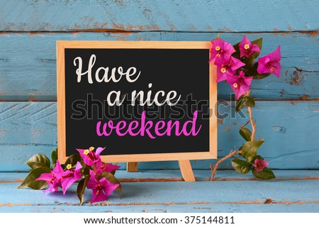 blackboard over blue wooden shelf with the phrase have a nice weekend - stock photo