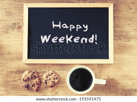 blackboard over wooden table with cup of coffee and cookies and the phrase happy weekend - stock photo