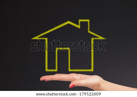 blackboard with chalk draw of house and woman hand - stock photo