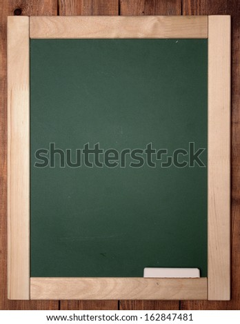 blackboard with chalk on wooden background - stock photo