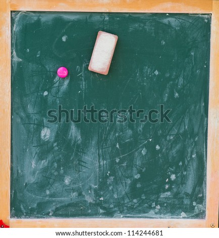Blackboard with eraser and chalk traces. - stock photo