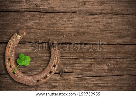 Blackboard with four-leaved clover and a horse shoe - stock photo