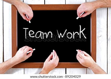 Blackboard with hands writing teamwork message - stock photo