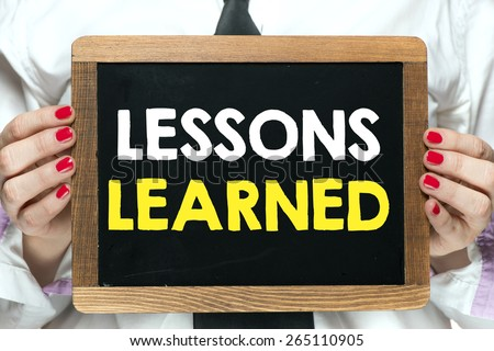 Blackboard with lessons learned. Hands holding blackboard with handwritten lessons learned - stock photo