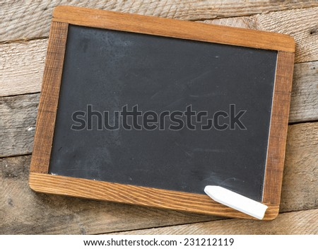 Blackboard with piece of chalk on wooden background - stock photo