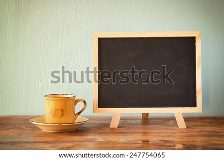 blackboard with room for text next to cup of coffee over wooden table, filtered image. - stock photo