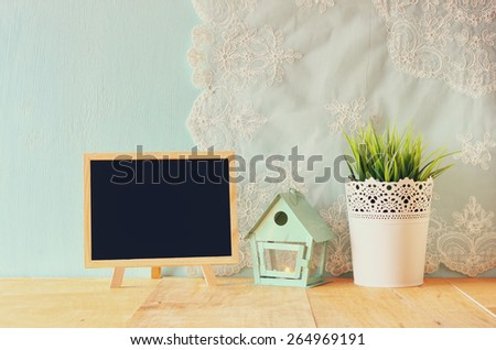 blackboard with room for text, vintage Flower pot and lantern as a bird house against mint wall and antique lace fabric - stock photo