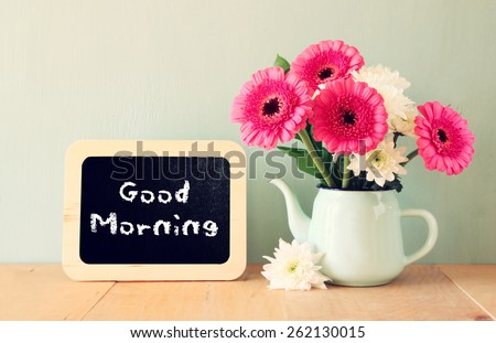 blackboard with the phrase good morning written on it next to vase with fresh flowers - stock photo