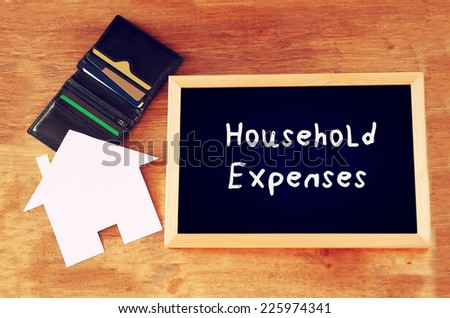 blackboard with the phrase household expenses, paper house shape and wallet with credit cards - stock photo