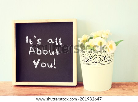 blackboard with the phrase it's all about you written on it  over wooden table