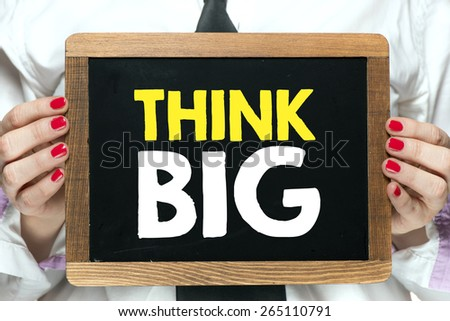 Blackboard with think big. Hands holding blackboard with handwritten think big