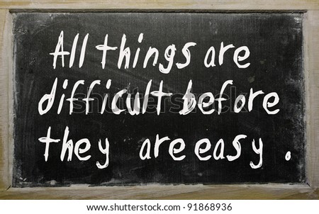 """Blackboard writings """" All things are difficult before they are easy """" - stock photo"""