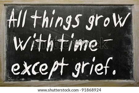 "Blackboard writings "" All things grow with time except grief "" - stock photo"