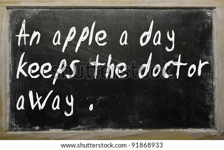 "Blackboard writings "" An apple a day keeps the doctor away"" - stock photo"