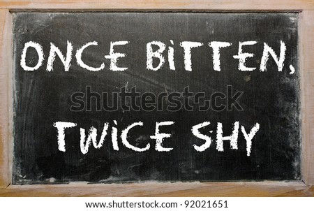 "Blackboard writings ""Once bitten, twice shy"" - stock photo"