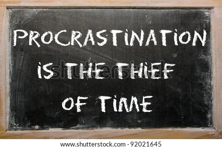 """Blackboard writings """"Procrastination is the thief of time"""" - stock photo"""