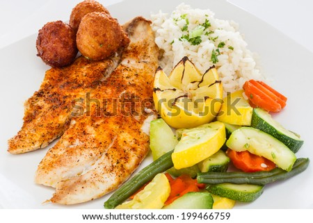 Blackened fish served with rice, vegetable medley, and hush puppies. - stock photo