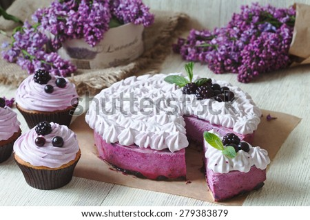 Blackerry purple souffle cake. Traditional delicious homemade baked sweet decorated with blackberry and whipped cream. Rustic style, natural light. Lilac flowers on background. - stock photo