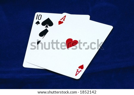 Blackjack! Closeup of Blackjack against a blue background.  Ten (10) of Spades behind Ace of Hearts. - stock photo