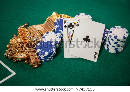 Blackjack 21 hand of a King and an Ace playing Cards on Casino green felt with chips and gold jewelry - stock photo
