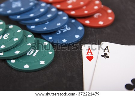 Blackjack playing cards (the ace of clubs and the ace of hearts) and casino poker chips on black background