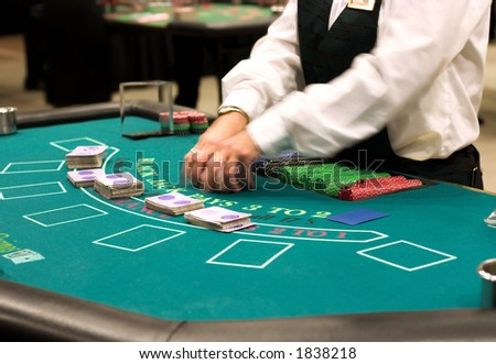 blackjack table at the casino, dealer shifting cards - stock photo