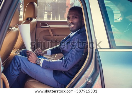 Blackman in a suit in the car. - stock photo