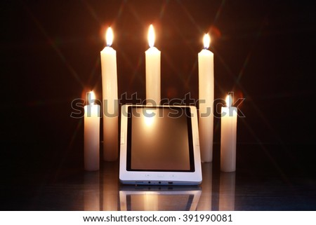 Blackout concept. Lighting candles around tablet like a sanctuary - stock photo