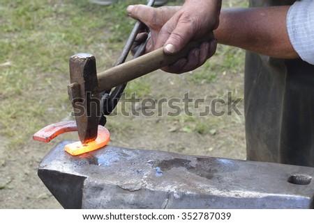 Blacksmith forges a horseshoe. - stock photo