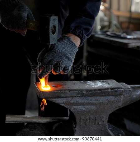Blacksmith forges a red-hot iron in the forge - stock photo