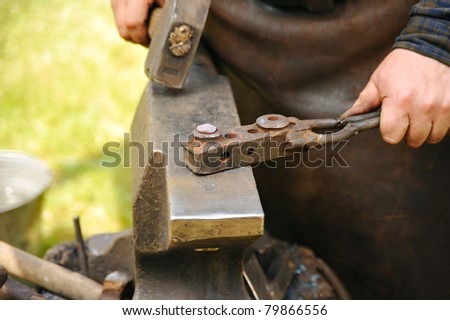 Blacksmith hammering hot steel on anvil - stock photo