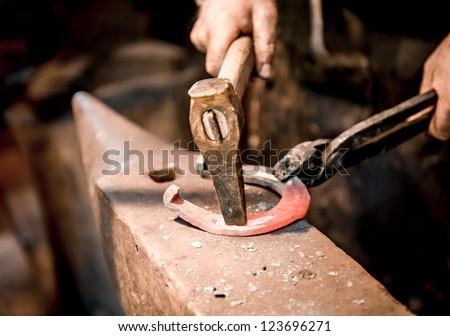 Blacksmith make a horseshoe - stock photo
