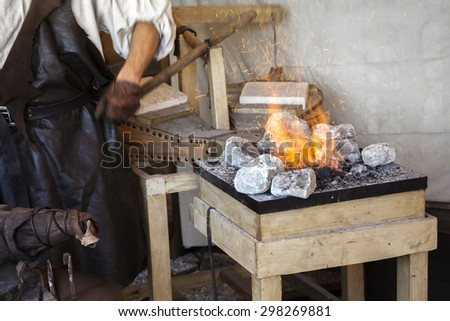 Blacksmith old-fashioned way of making articles of iron - stock photo