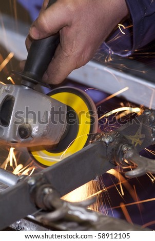 Blacksmith uses a grinder that does sparks - stock photo
