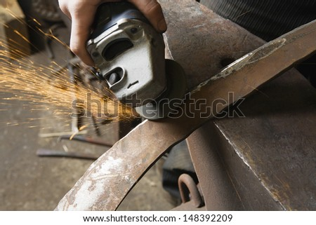 Blacksmith using angle grinder on edge of metal tool in workshop - stock photo
